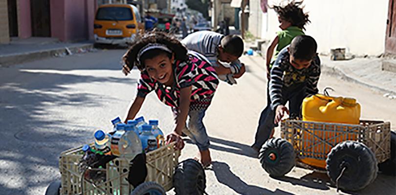 Niños empujando agua