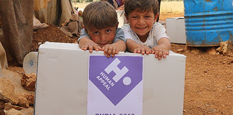 two small boys leaning on a human appeal box - syria